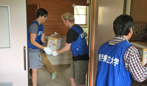 In the foreground inside the door frame: OHIO Sophomore Nick Farris and Senior Ben Piper help unload boxes of Itoen water and tea from a truck into a storage area as part of the OHIO-IPU Tsunami Volunteer Project Project year six.