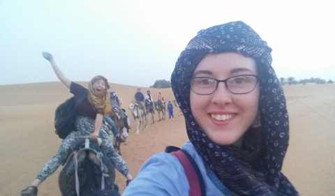 Mica Smith takes a selfie while riding a camel in the Sahara Desert.