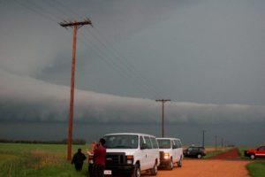 Vans parked alongside field, storm clouds overhead