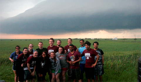 Dr. Jana Houser led 12 undergraduates and two graduates on a storm-chasing trek through the Central Plains. Shown here standing in a field as a group with storm clouds behind them.