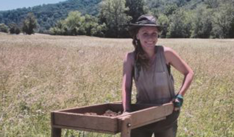 Tatiana Fox at archaeological site standing at sifter