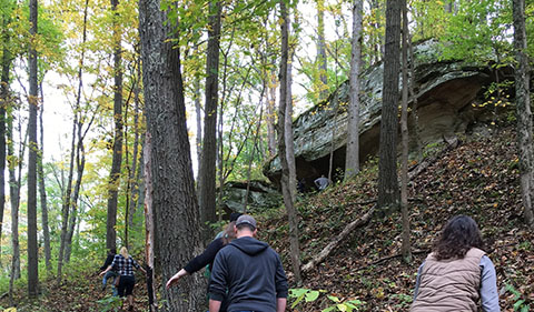 Alumni, students, and guests approaching the Facing Monday Creek Rock Shelter on the Relive the Dig! Field Site Tour