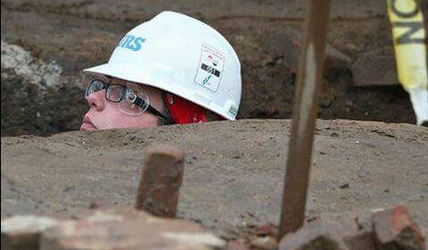 Ashley Taylor in hard hat, head sticking up out of what appears to be a street excavation