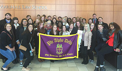 Phi Alpha Delta touring John Marshall Law School in Chicago. Big group poses around Phi Alpha Delta banner.