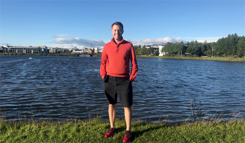 Christopher Myers in Reykjavik, Iceland, in running gear with lake in background