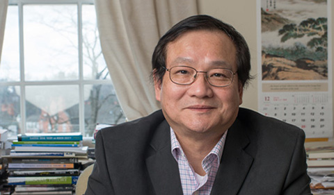 Jieli Li at his office desk with books and window behind him