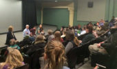 Panelists engage a packed theater at the Athena.