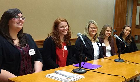 Ashley Taylor, Megan Norris, Jen Winner, Hannah Vaughn, Ellie Koewler sitting behind table with two microphones