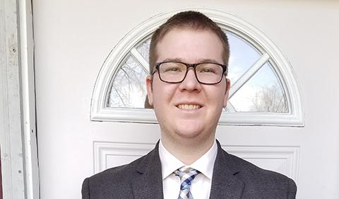 Zach Walden in suit and tie with front door behind him