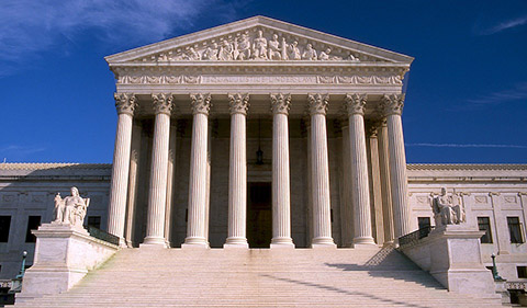 Front view of the Supreme Court of the United States on a clear day with blue sky behind