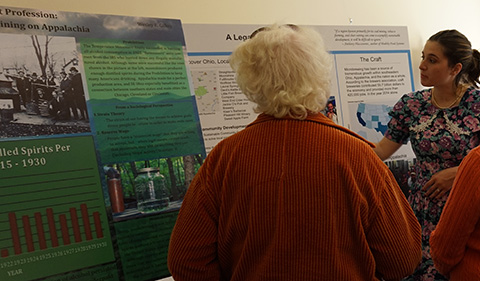 Toshia Edge discussing her research with visitors at Spirits of the Little Cities: Temperance & Taverns, the 22nd Annual Little Cities of Black Diamonds Day in October 2016; poster is in the image.