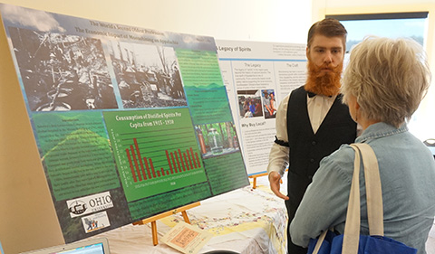 Wes Gilkey in costume discussing his research with a visitor to Spirits of the Little Cities: Temperance & Taverns, the 22nd Annual Little Cities of Black Diamonds Day in October 2016; poster is visible in this image.