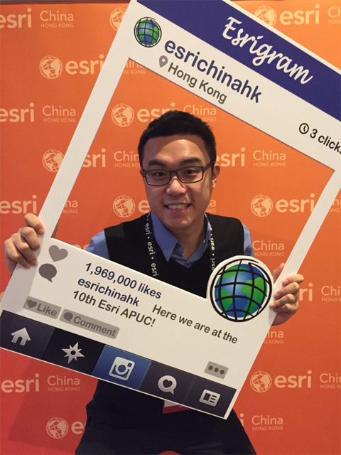 Lo attending the 2015 Asia Pacific User Conference. Man standing in frame with orange background.