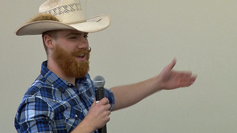 Wes Gilkey in straw hat holding microphone and arm out to his side in sweeping gesture Wes Gilkey