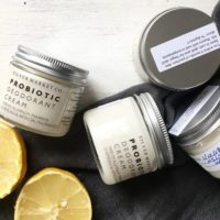 small jars of SM Co. Probiotic Deodorant Cream and a cut open lemon