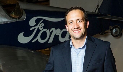 Christian Cullen standing in front of an airplane with the Ford logo on the side