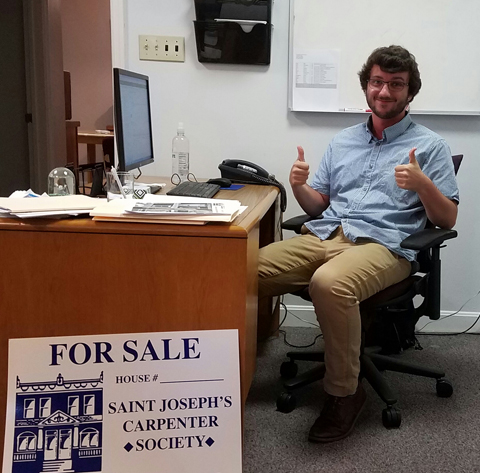 Kees Vande Stadt at his internship in Saint Joseph's Carpenter Society is a nonprofit organization in East Camden, NJ. he is shown sitting at a desk with two thumbs up.