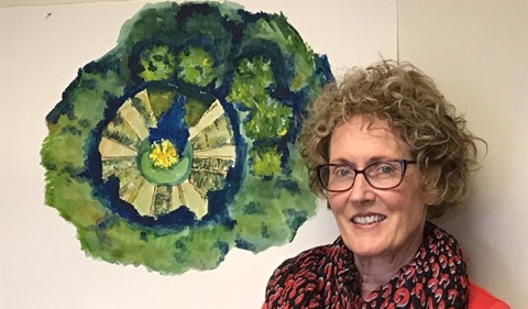 Dr. Theresa Moran, Food Studies Theme Director, stands next to student art depicting a garden where students grow produce now offered in campus venues.