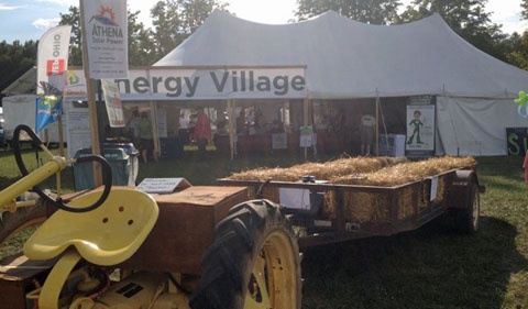 Energy Village at Pawpaw festival, with tractor in foreground pulling wagonload of pawpaws.