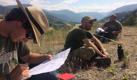 Geology students adding details to a geologic map in progress, while situated with mountains in the background.