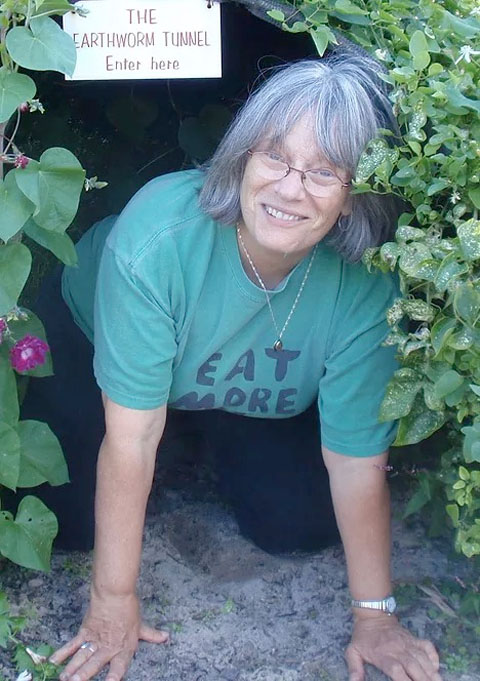 Author Grace Gershuny, framed by plants and sign that says The Earthworm tunnel enter here.
