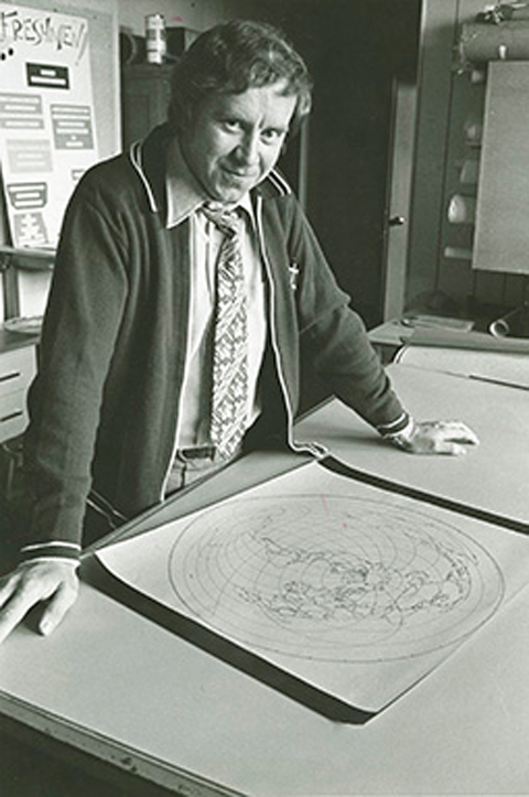 Dr. Hugh Bloemer, standing with a map in an old black and white photo
