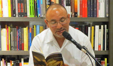 Dr. Daniel Torres, shown reading from a book