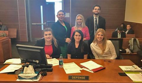 Defense team members seated L-R, Gabrielle Tharp, Sarah Horne, Alexa Jesser, standing L-R Hazel Minich, McKenzie Allen, and Noah Allen