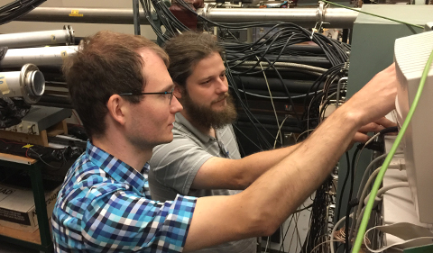 ND Postdoctoral Researchers Axel Boeltzig and Kevin Macon use an oscilloscope to visually inspect the signal coming from the detector.