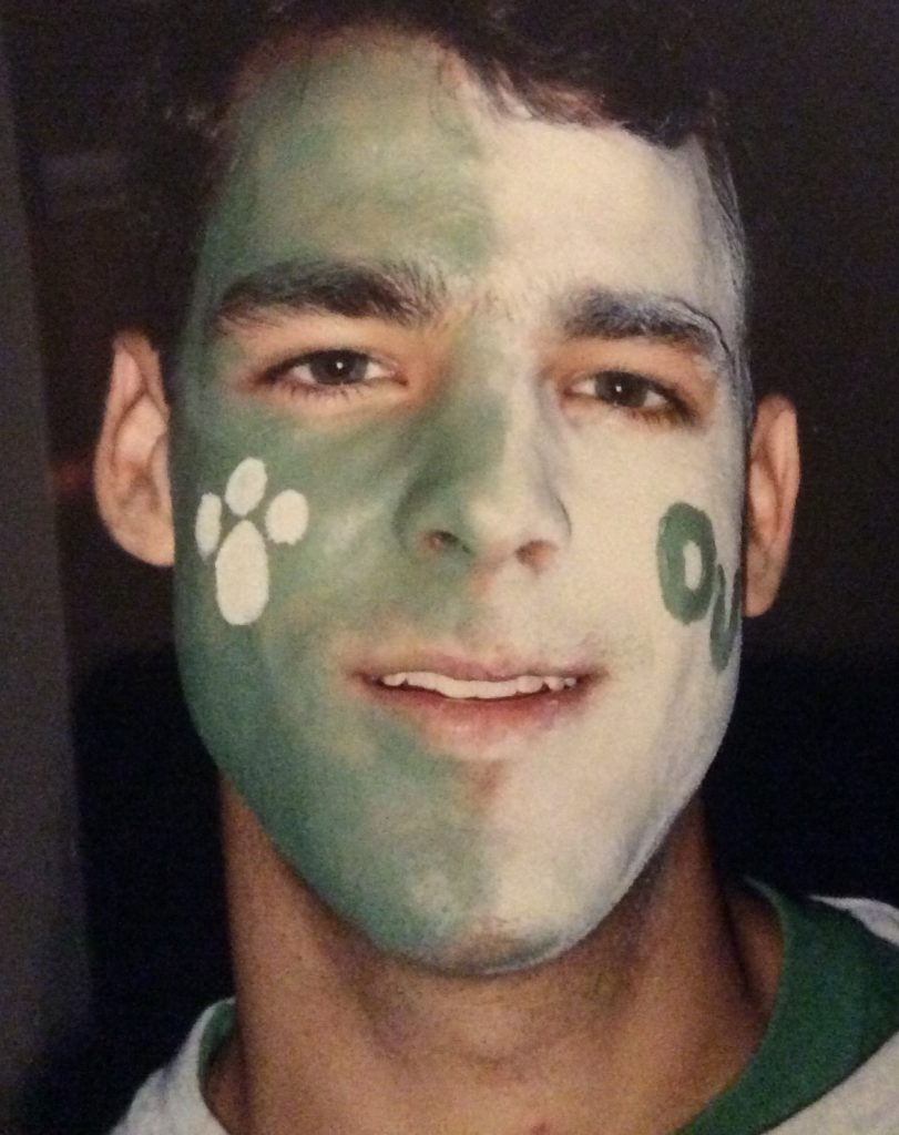 Headshot of man with green and white facepaint