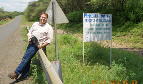 Michael Kukral leaning on guardrail, alongside a sign that says Perkeera Water Resource Users Association
