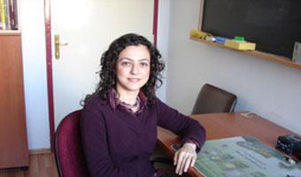 Dr. Pınar Aydoğdu, sitting at desk