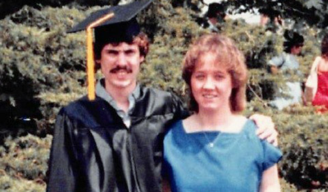 Richard Couch celebrates commencement., shown in cap and gown with a woman in a blue dress.