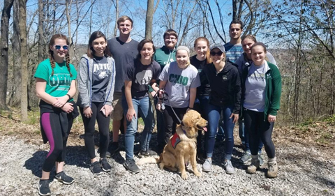 TriBeta officers and members enjoy a hike in the Athens area. Shown here in a group photo with a training dog.