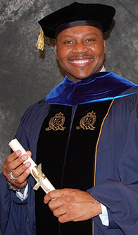 A smiling Dr. Jason Carthen in doctoral cap and gown holding his diploma