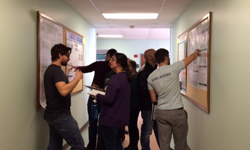 Scientific Writing poster session in Porter Hall, with students pointing at posters on both sides of hallway,