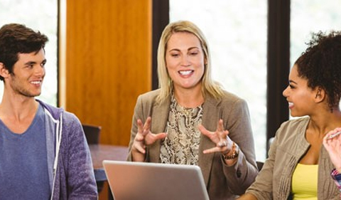 Photo of three teachers talking around a computer