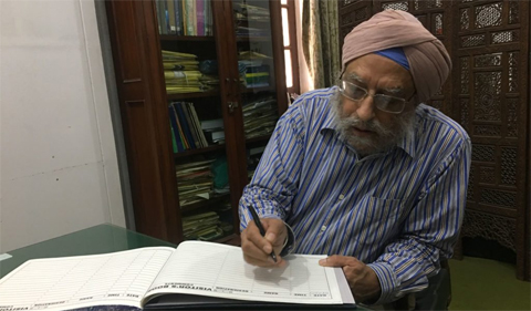 Dr. Amritjit Singh was given a tour of the Quaid-e-Azam Library and its holdings and facilities. He is shown here sitting at a table writing.