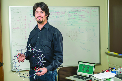 Eric Masson studies pumpkin-shaped Cucurbi-turil molecules, shown here holding a circular model in his hands