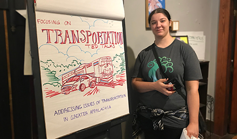 a smiling Samantha (Sai) Jones standing next to her poster presenting on Transportation at the 2017 Little Cities of Black Diamonds Day event in October 2017