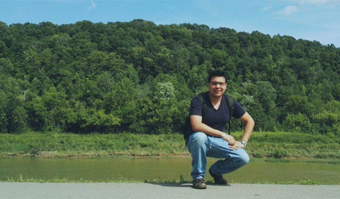 Ricardo Molina Herrera, wins first place in OPIE Writing Contest. shown here kneeling by a lake.
