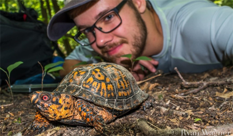Ryan Wagner takes a selfie with a turtle.