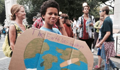 Happening: A Clean Energy Revolution documentary, boy holding sign saying the Earth has feelings