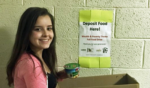 Lauren Conner with her food drive box and poster on wall saying Deposit Food Here!