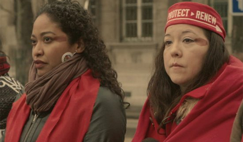 Not Without Us documentary, two women wearing protect and review bands.