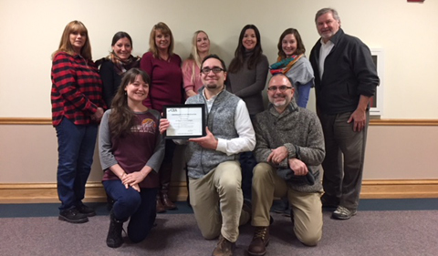 Faculty and staff in the Ohio Program of Intensive English pose for a photo with the certificate they received from the Commission on English Language Program Accreditation acknowledging the program's initial five-year accreditation.