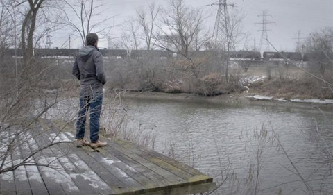 WHAT LIES UPSTREAM: WATER AND SOIL TESTING CAMPAIGN, man standing on dock along river.
