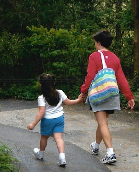 Woman holding child's hand, walking outdoors