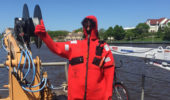 """Jack Bruno participates in a day-long safety training session wearing a """"dry suit"""" as he poses on the deck of a NOAA research vessel."""