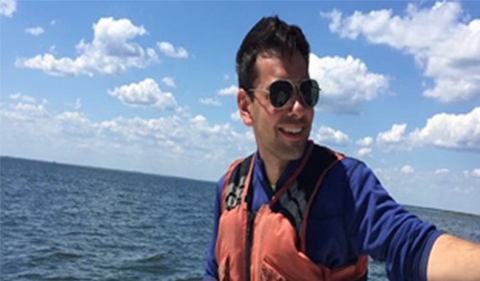 Daniel Leger, portrait outdoors, wearing life jacket on boat